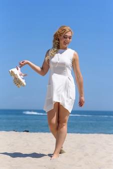 Het meisje in een witte kleding loopt langs het strand dat haar schoenen uittrekt