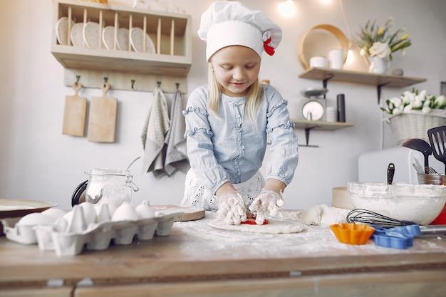 Het meisje in een witte shefhoed kookt het deeg voor koekjes
