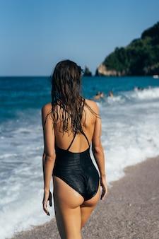 Het meisje in een zwart zwempak aan zee. achteraanzicht