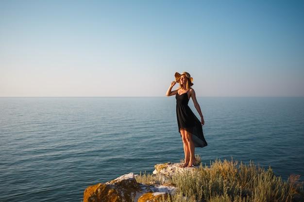 Het meisje in een zwarte jurk en hoed op een rotsachtig strand kijkt naar de zee