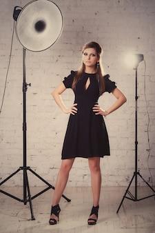 Het meisje in een zwarte kleding bevindt zich in studio op witte bakstenen muurachtergrond