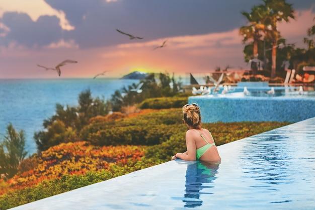 Het meisje in een zwembroek in het zwembad kijken naar de zonsondergang aan de zee. achteraanzicht, levensstijl