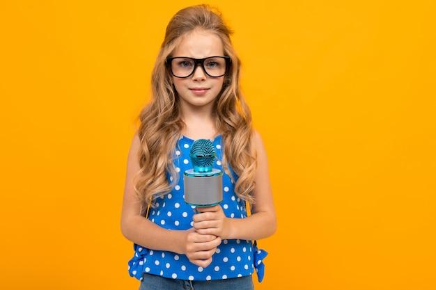 Het meisje in glazen houdt een microfoon op een oranje achtergrond