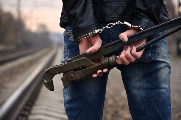 Het meisje in handboeien met de pijpmoersleutel op de spoorweg