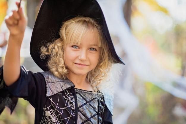 Het meisje in heksenkostuum viert halloween openlucht en heeft pret.