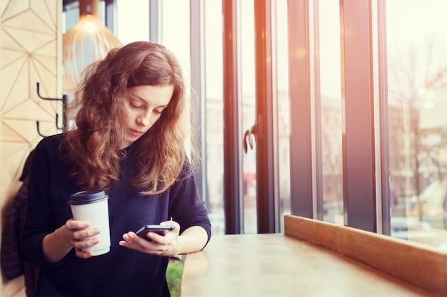 Het meisje in het café drinkt koffie en gebruikt de telefoon