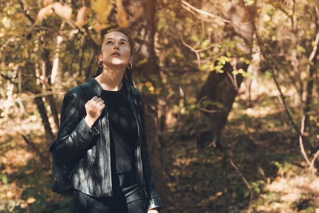 Het meisje in het de herfstbos kijkt omhoog. alleen met gedachten. gouden herfst.