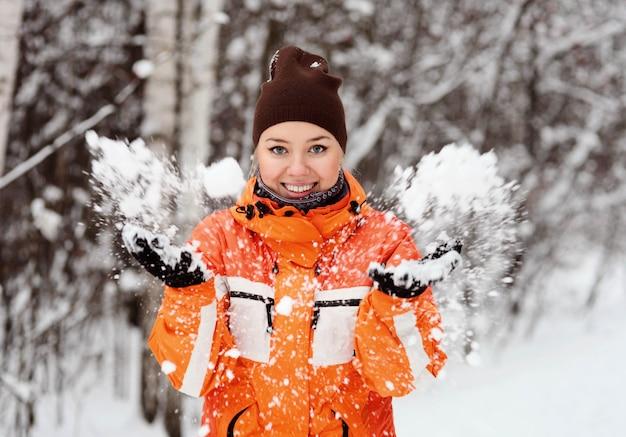 Het meisje in het de winterbos werpt sneeuw en glimlacht. blij gezicht.