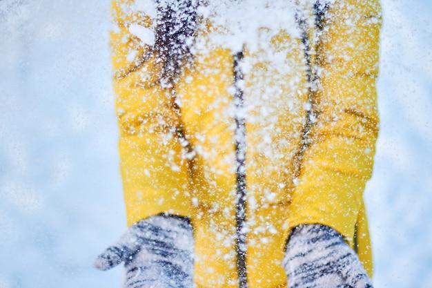 Het meisje in het gele jasje werpt sneeuw in de lucht bij koud weer. vrolijke winterstemming bij vrouwen
