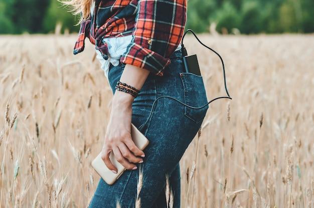 Het meisje in het gele veld laadt de telefoon op van de powerbank.