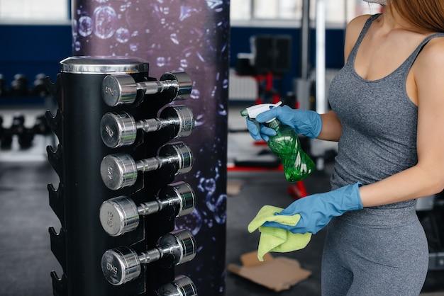 Het meisje in het masker desinfecteert de fitnessapparatuur tijdens een pandemie.