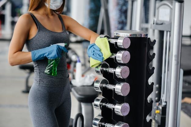 Het meisje in het masker desinfecteert de fitnessapparatuur tijdens een pandemie