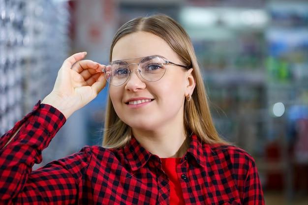Het meisje in het shirt doet een bril uit en meet zichzelf op