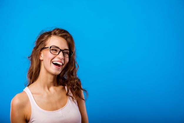Het meisje in het t-shirt en de bril glimlacht en lacht.