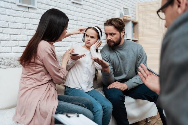 Het meisje in hoofdtelefoons negeert de therapiezitting van ouders