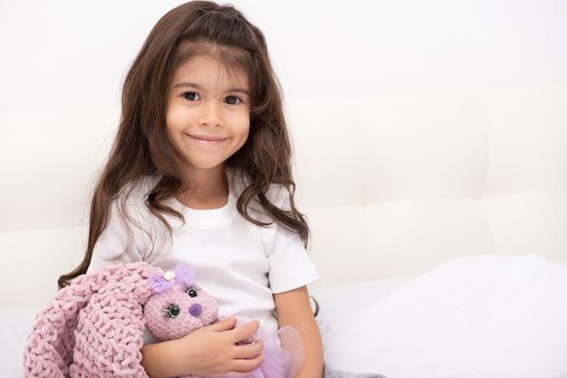 Het meisje in huiskleding zit met teddykonijntje thuis op bed.