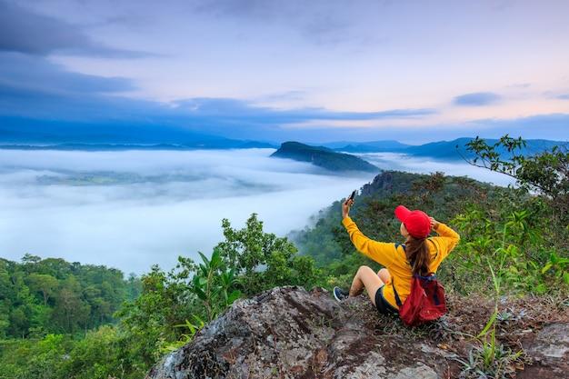 Het meisje in jas staande op de berg