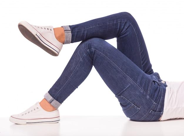 Het meisje in jeans ligt op een witte vloer.