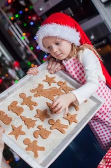 Het meisje in kerstmanhoed toont haar koekjes van de kerstmispeperkoek