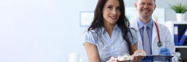 Het meisje in kliniek houdt borstimplantaten dichtbij arts