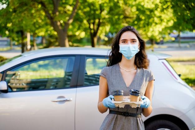 Het meisje in medisch masker en handschoenen houdt dienblad met wegwerpkoffiekopjes