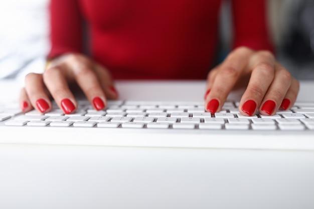 Het meisje in rode kleren klikt op het toetsenbordclose-up