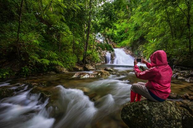 Het meisje in rode trui touring op pi-tu-gro waterval, prachtige waterval in de provincie tak, thailand.