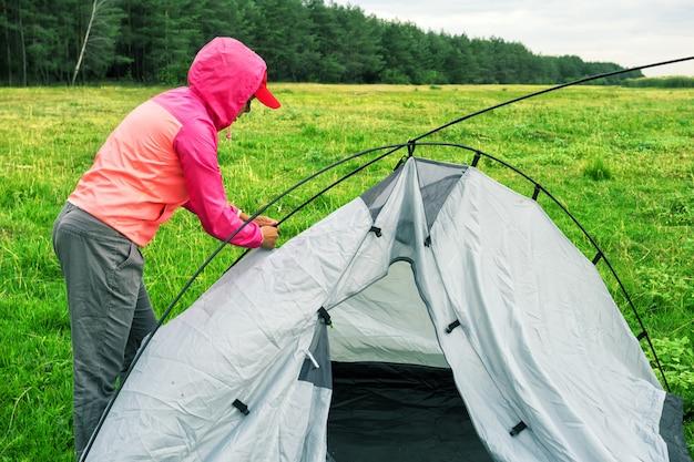 Het meisje in roze jasje en glb verzamelt tent op groen gebied