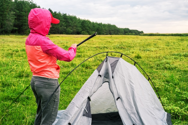 Het meisje in roze jasje met kap zet tent op