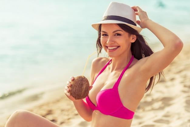 Het meisje in roze zwempak en hoed drinkt kokosmelk.