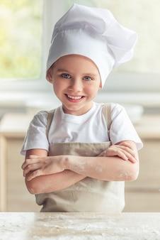 Het meisje in schort en chef-kokhoed bekijkt camera en het glimlachen.