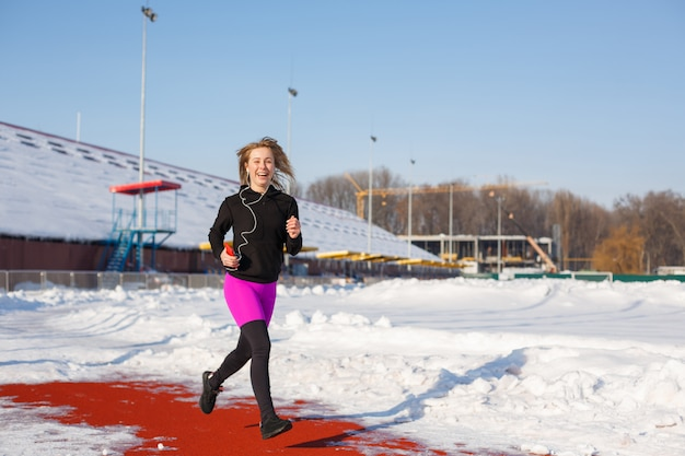 Het meisje in sportkleding loopt op het rode spoor voor het lopen op een met sneeuw bedekt stadion fit en sportlevensstijl