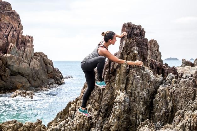 Het meisje in sportkleding op de rotsen