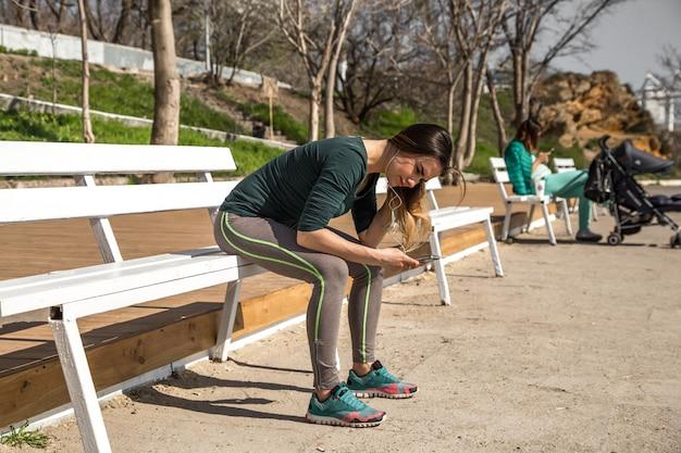 Het meisje in sportkleding op een bankje luisteren naar muziek