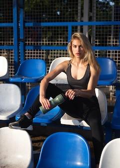 Het meisje in sportkleding zit op het podium met een fles water