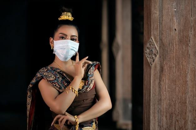 Het meisje in thaise klederdracht draagt een masker, dansen in een gesloten positie. coronaviruspreventie