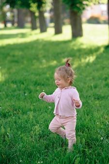 Het meisje in vrijetijdskleding maakt haar eerste stappen op het gras