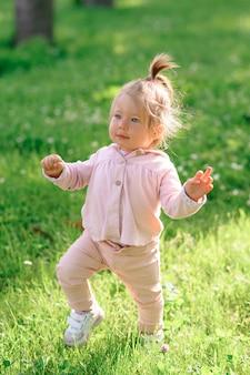 Het meisje in vrijetijdskleding maakt haar eerste stappen op het gras.