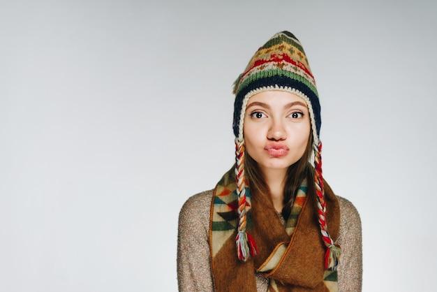 Het meisje in warme kleren beledigde haar lippen en kijkt voor zich uit. lichte achtergrond