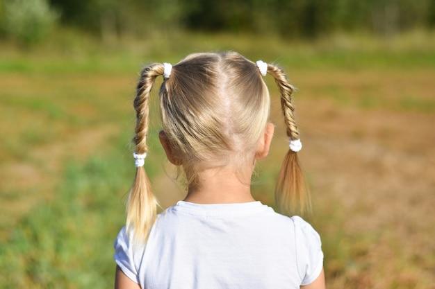 Het meisje in witte kleding kijkt vooruit op het gebied, achtermening, close-up