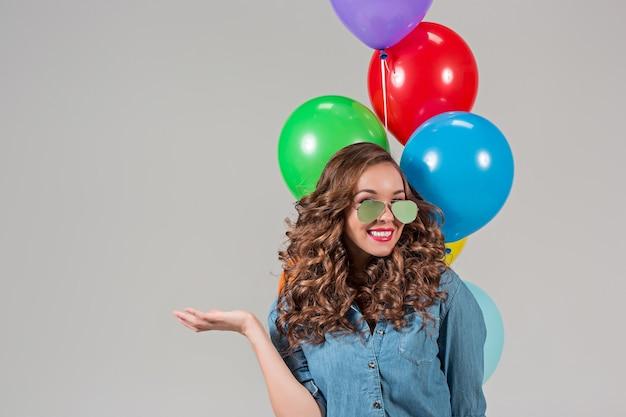 Het meisje in zonnebrillen en een heleboel kleurrijke ballonnen op grijs