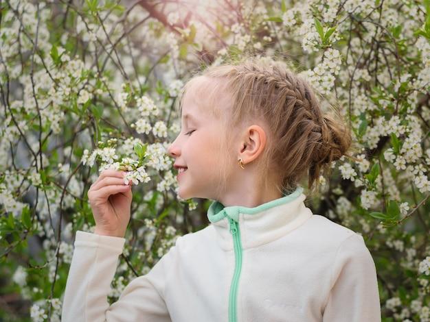 Het meisje inhaleert de geur van verse kersen in de lentetuin