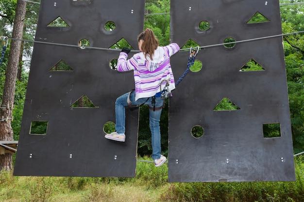 Het meisje is 10 jaar oud in hoog klimpark avonturenklimmen