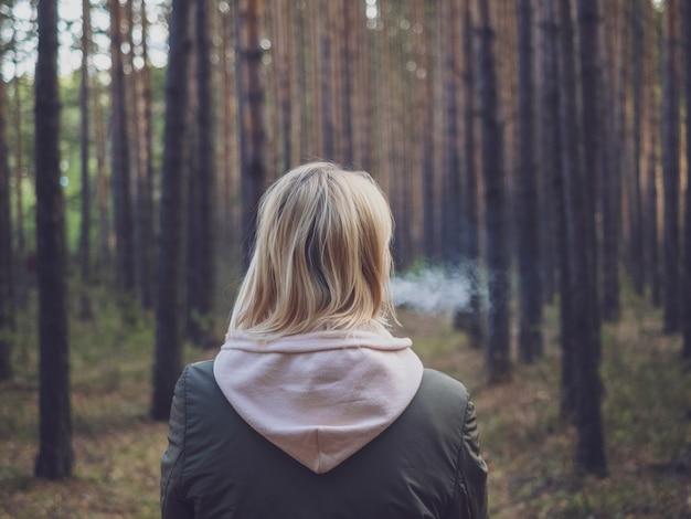 Het meisje is blond, haar gezicht is niet zichtbaar, roken in het bos in de frisse lucht.