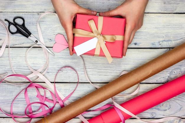Het meisje is een cadeau aan het inpakken. op een lichttafel ligt een cadeautje, inpakpapier, plakband en een schaar.