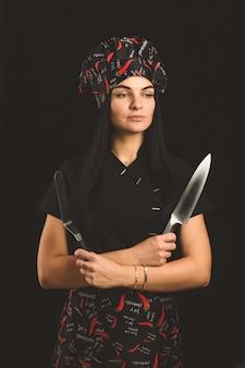 Het meisje is een professionele kok met een mes en hete peper.