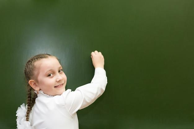 Het meisje is een student van elementaire elementaire graden schrijft een klein schoolbestuur.