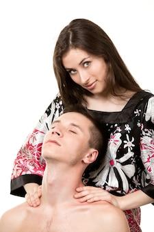 Het meisje is gekleed in een veelkleurige blouse en kijkt naar de camera, doet nekmassage aan man met naakte torso