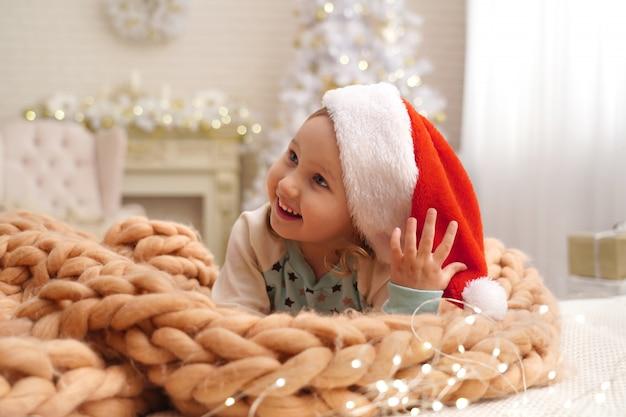 Het meisje is klein met een designdeken gemaakt van natuurlijke beige wol. achter het meisje op de achtergrond staat een kerstboom bij het raam.