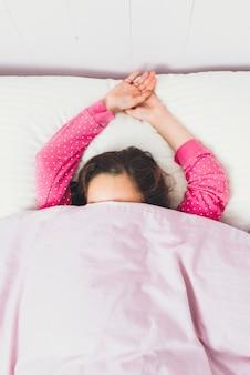 Het meisje is net wakker geworden met haar gezicht bedekt met een deken omdat ze niet naar school wil.